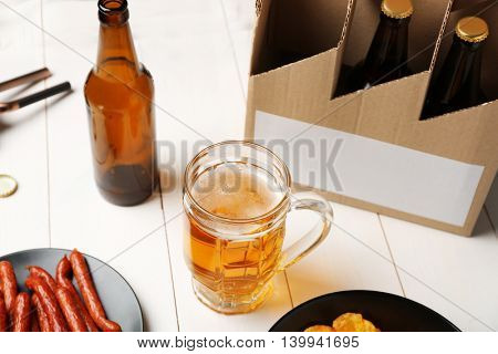 Mug of beer with snack and paper package on wooden background