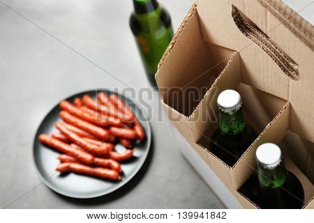 Paper beer package with sausages on grey background