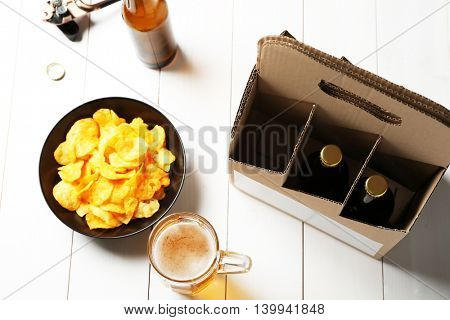 Paper beer package with mug and chips on wooden background