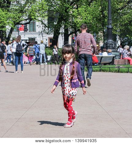 St. Petersburg, Russia - 9 May, Little girl with pigtails, 9 May, 2016. Vacationers people on the lawns and gardens in the city.