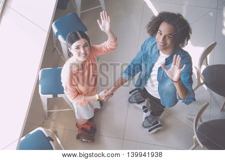 Hello. Happy and smiling young people riding hoverboards while being indoors in a cafe, posing while joining hands and waving