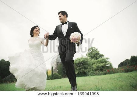 Newly married couple running and jumping in park while holding hands.