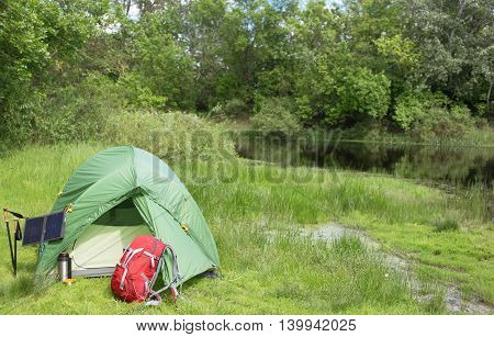 Camping in the woods with a backpack and a tent on the banks of the river in the summer.