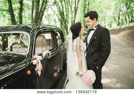 Beautiful newlywed couple posing near retro black car.
