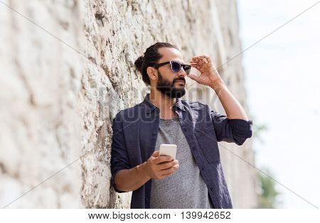 leisure, technology, communication and people concept - man with smartphone at stone wall