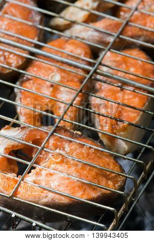 tasty pieces of salmon with spices cooking on a grill