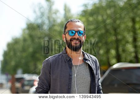 people, music, technology, leisure and lifestyle - hipster man with earphones walking along city street and listening to music