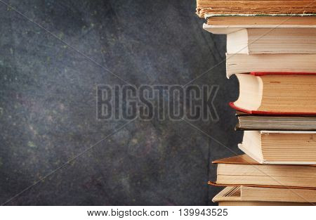 Books in front of chalk board. Back to school concept with copy space