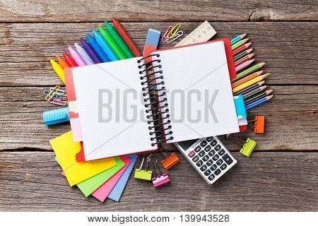 Notepad for your text over colorful supplies on wooden table. Back to school concept with copy space