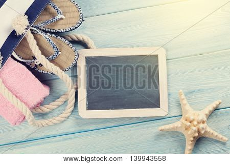Beach accessories. Bag with flip-flops and towel and blackboard for your text on wooden background. Top view with copy space. Sunny toned