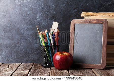 Books, supplies and chalk board for your text. Back to school concept with copy space