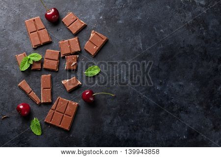 Chocolate and cherry berries on dark stone background. Top view with copy space