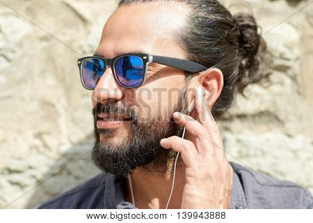 people, music, technology, leisure and lifestyle - hipster man with earphones and listening to music outdoors