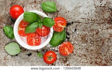 Cherry tomatoes fresh basil leaves salt and black pepper on old metal background. Italian food composition top view blank space for text
