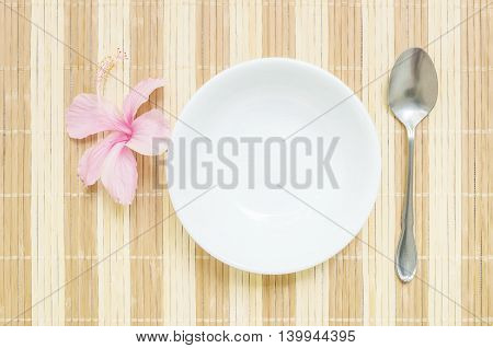Closeup white ceramic cup for soup with stainless spoon and pink flower on blurred wood mat textured background