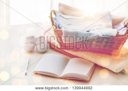 motherhood, care, parenthood and object concept - close up of pile of baby clothes with towel for newborn boy in basket and blank notebook or diary on table