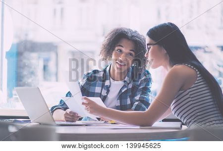 During informal meeting. Cheerful young man and serious young woman holding papers and discussing something during their meeting