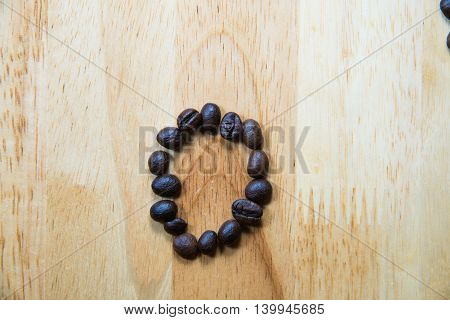 Alphabet O Make From Coffee Bean On Wood Background