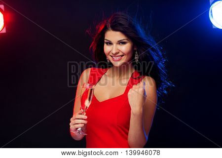 people, holidays, party, night lifestyle and leisure concept - beautiful sexy woman in red dress with champagne glass at nightclub