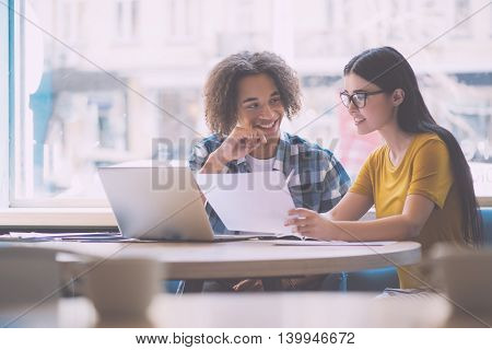Fall in love with colleague. Positive and merry young coworkers working with some papers while sitting at the table together