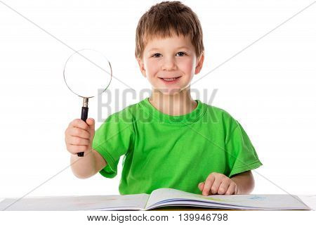 Inspired little boy at the table with magnifier in hands, isolated on white