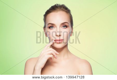 beauty, people and plastic surgery concept - beautiful young woman showing her lips over green background