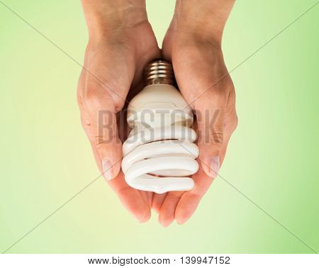 recycling, electricity, environment and ecology concept - close up of hands holding energy saving lightbulb or lamp over green background