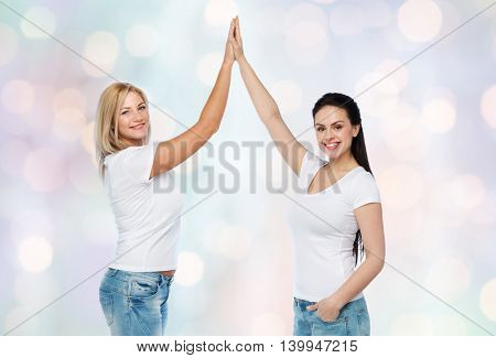 friendship, diverse, body positive, gesture and people concept - group of happy different women in white t-shirts making high five over holidays lights background