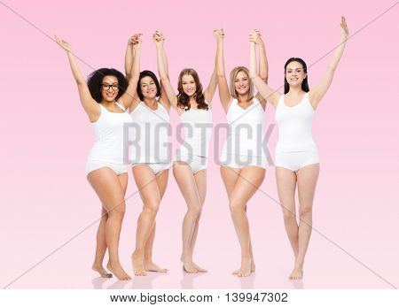 happiness, friendship, beauty, body positive and people concept - group of happy different women in white underwear with raised arms celebrating victory over pink background