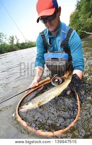 Closeup of brown trout fish, net, fishing rod, set by river