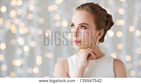 jewelry, luxury, wedding and people concept - smiling woman in white dress with diamond earring over holidays lights background