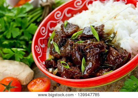Mongolian meat in sauce with rice. Traditional Asian dish stir-fry selective focus