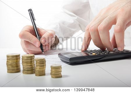 Business concept. Businessman's hand counting money on calculator and signing documents at office workplace, office work. Stack of coins. Financial Accounting - money and calculator