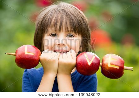 Cute Little Child, Boy, Holding A Love Sign, Made From Apples, Letter Graved In The Apple