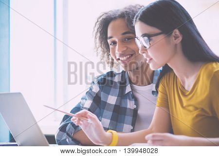 Teamwork. Cheerful and delighted young businessman smiling at a camera with his female colleague working with laptop in foreground