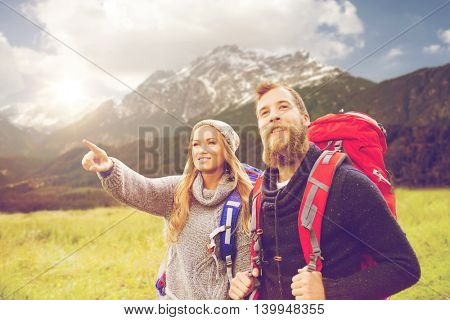 adventure, travel, tourism, hike and people concept - smiling couple walking with backpacks over alpine mountains and hills background
