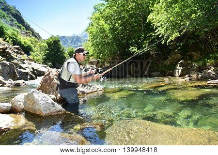 Fisherman trout fishing with bait in mountain river