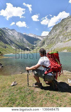 Hiker relaxing by Ossoue lake, Cirque de Gavarnie