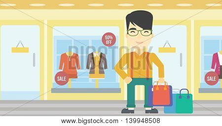 An asian man holding shopping bags on the background of boutique window with dressed mannequins. Happy young man carrying shopping bags. Vector flat design illustration. Horizontal layout.