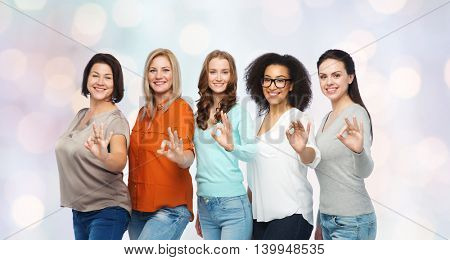 friendship, fashion, body positive, gesture and people concept - group of happy different size women in casual clothes showing ok hand sign over holidays lights background