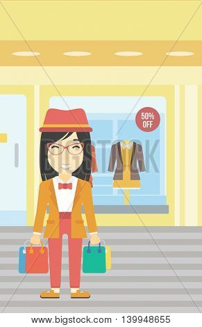 An asian woman holding shopping bags on the background of boutique window with dressed mannequins. Happy young woman carrying shopping bags. Vector flat design illustration. Vertical layout.