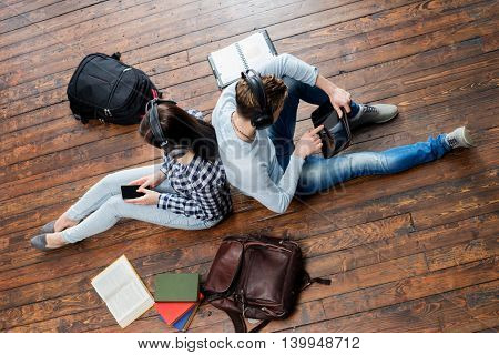 Girl using a smartphone and boy using a tablet in headphones listening to the music and leaning on each other on wooden floor having notebooks and bags around them.