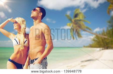people, summer holidays, travel and vacation concept - happy couple over exotic tropical beach with palm trees background