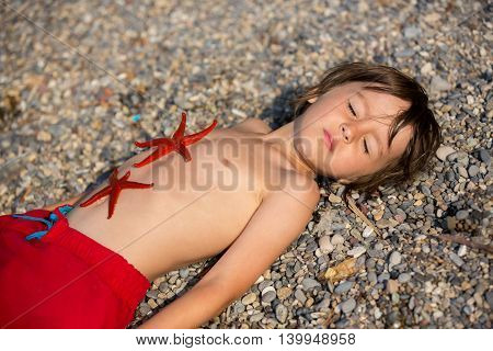 Adorable Little Boy, Lying In The Sand On The Beach, Two Red Starfishes Lying Down