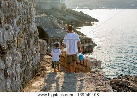 Father and son walking hand in hand on a sea coast path next to Mediterranean sea in France