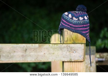 Lost hat on wooden fence post. Wooly child's hat mislaid in countryside placed on gate in hope of being seen by owner