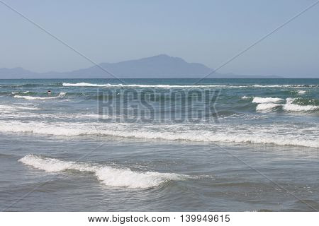 Mediterranean Sea with blue summer wave background. Beautiful water nature. Sea waves on beach. Blue sea and cloudless sky.