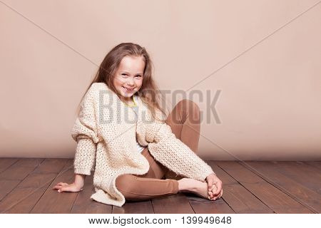 a little girl sitting on the floor and smiles