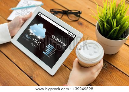 business, weather cast, technology, people and advertisement concept - close up of woman with forecast on tablet pc computer screen and coffee cup on wooden table
