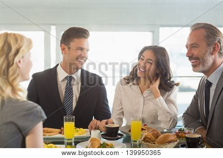 Business people interacting with eachother while having meal in restaurant